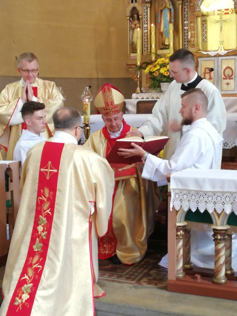 Piotr Kowalczyk klęczy przed biskupem